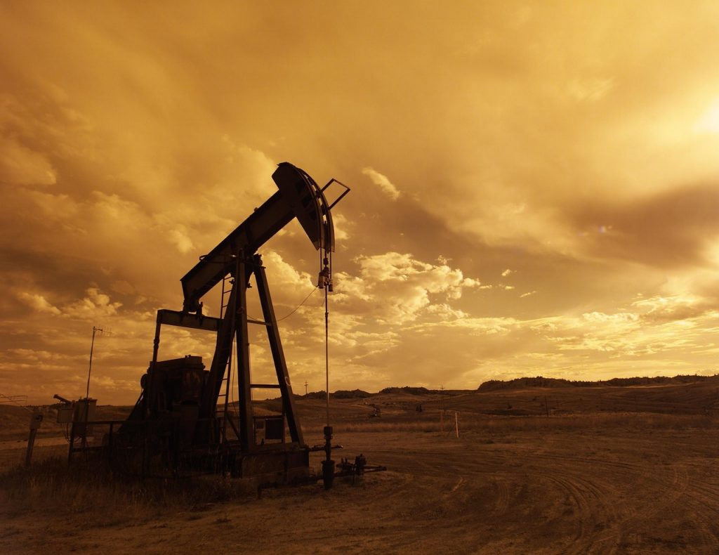 Energy oil pump jack in field at sunset