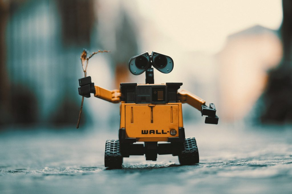 Technology small robot holding a plant on street with background blurred